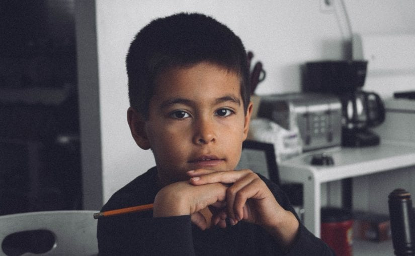 boy with black long-sleeved shirt holding pencil inside room