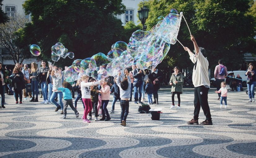children playing in park with bubbles